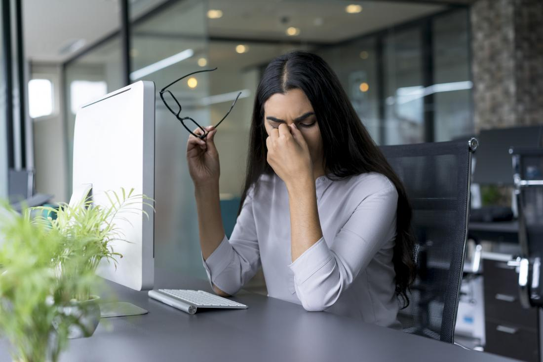 Woman with headaches stress pain at work, pinching bridge of nose.