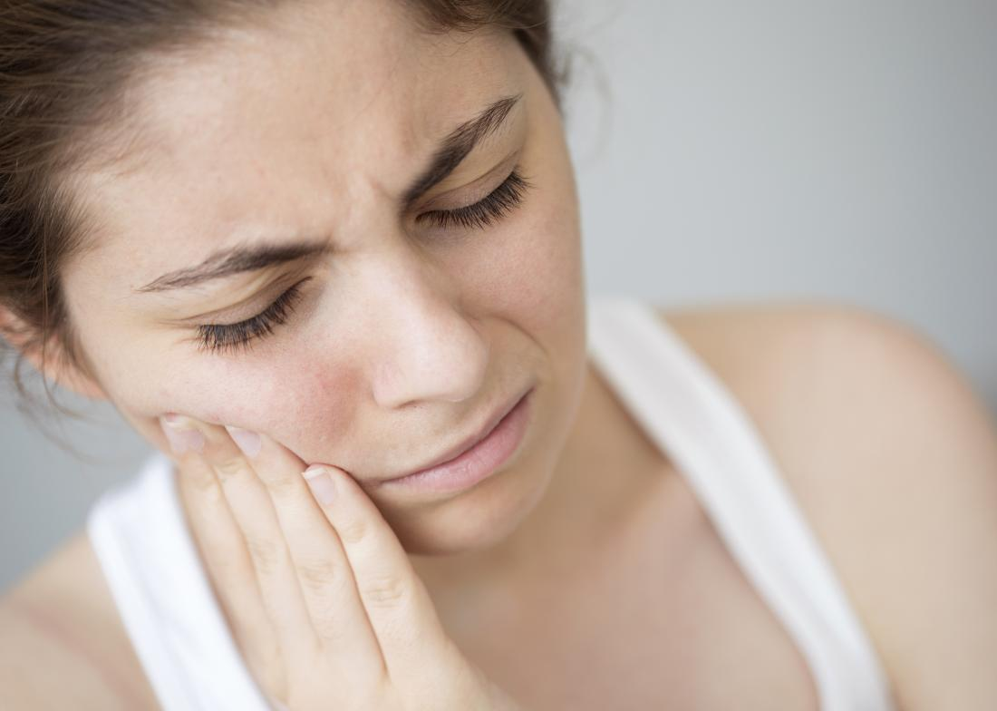 Root canal pain with woman holding side of mouth because of toothache