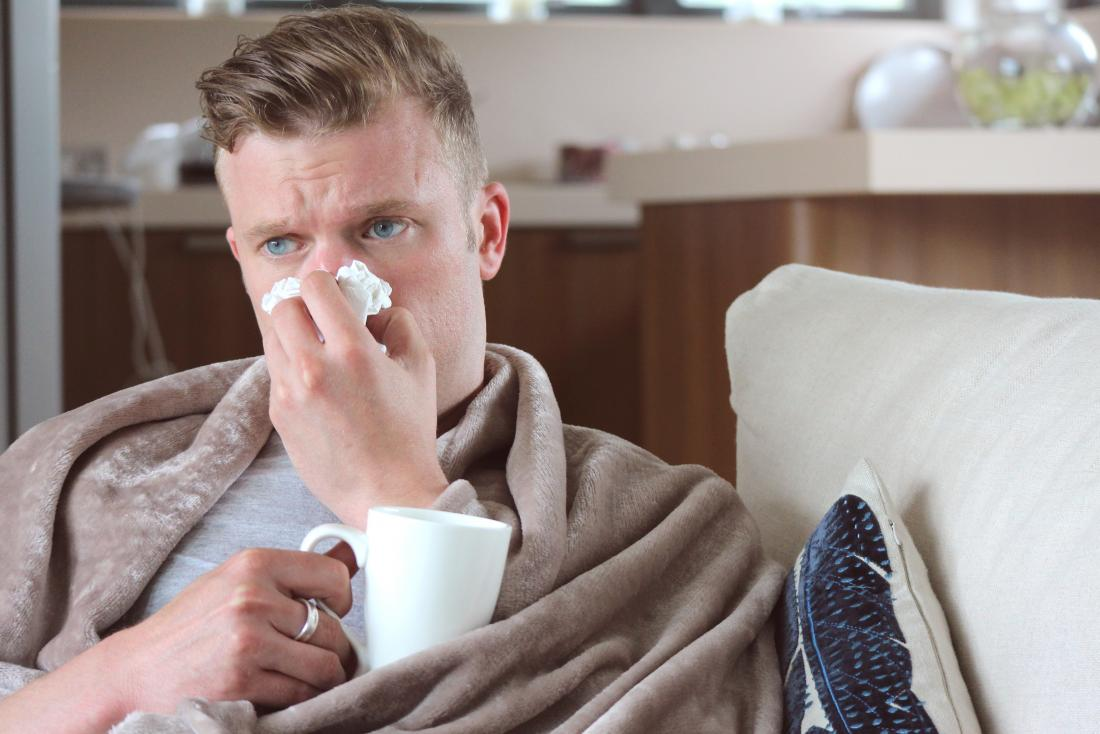 Man with runny nose drinking hot drink at home under blanket on sofa.