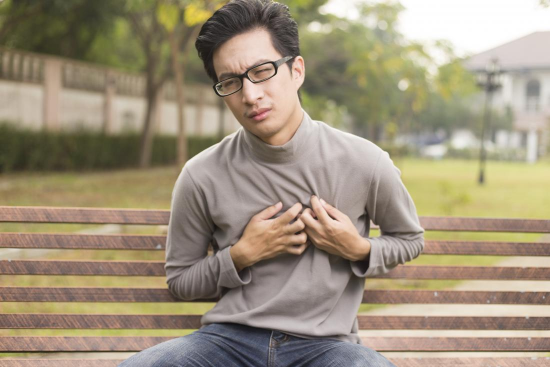 young man with chest pain sitting on bench in park