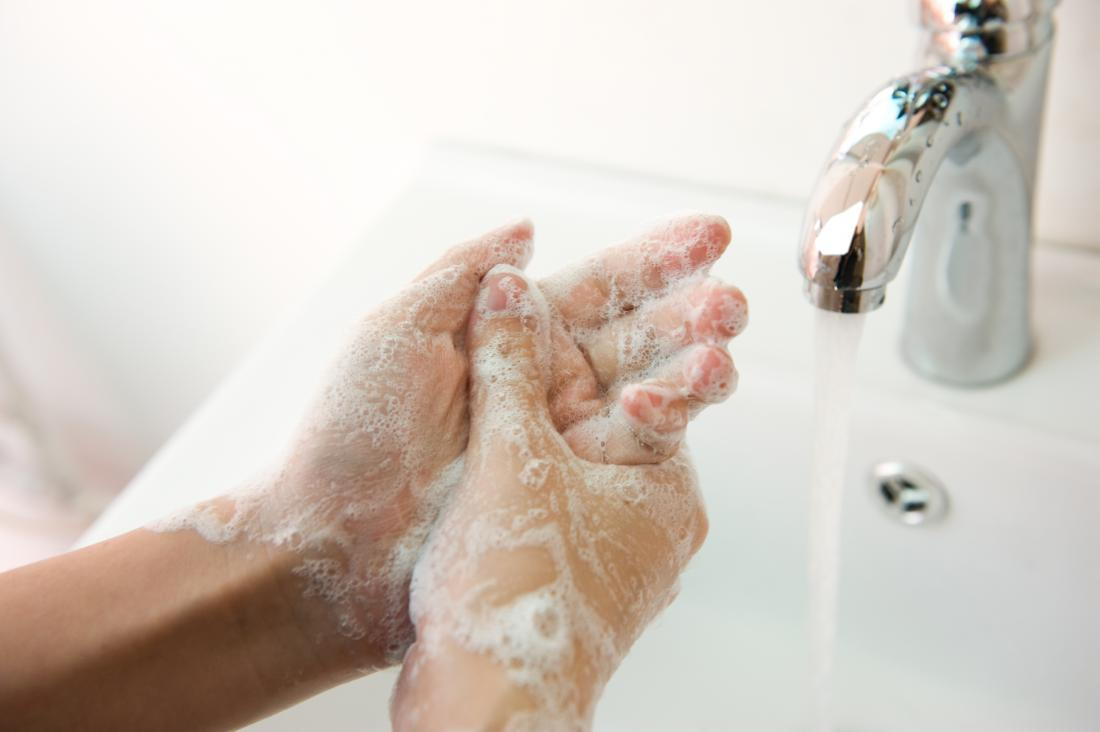 woman washing her hands with soap and water
