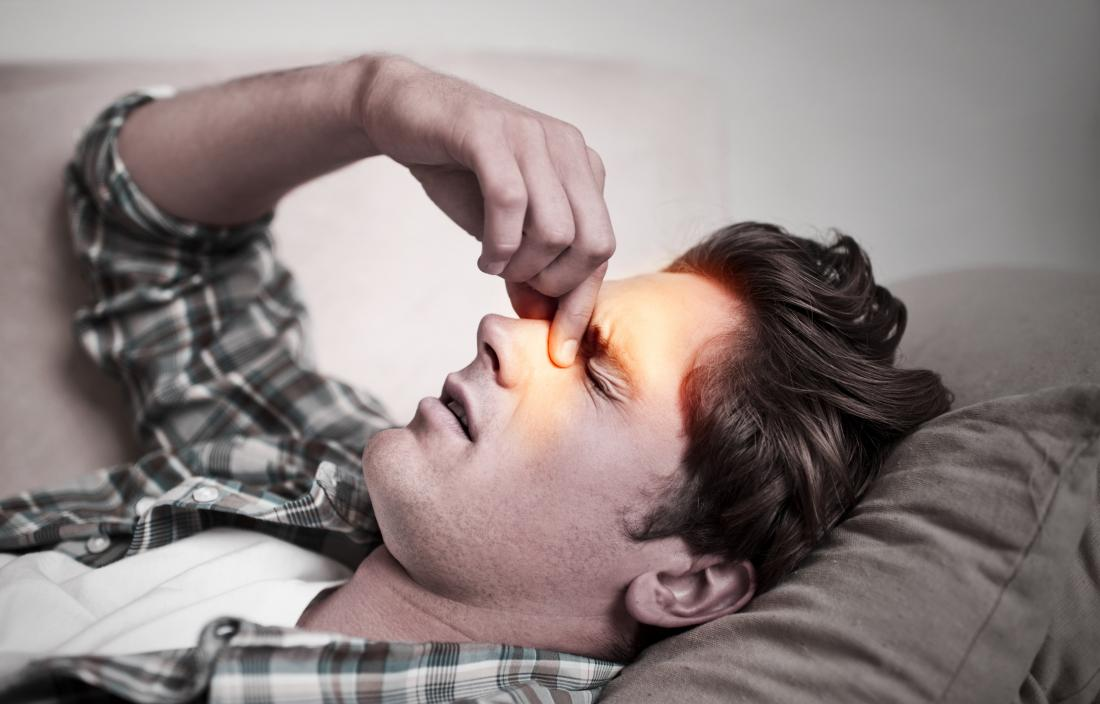 man holding his nose due to a sinus headache