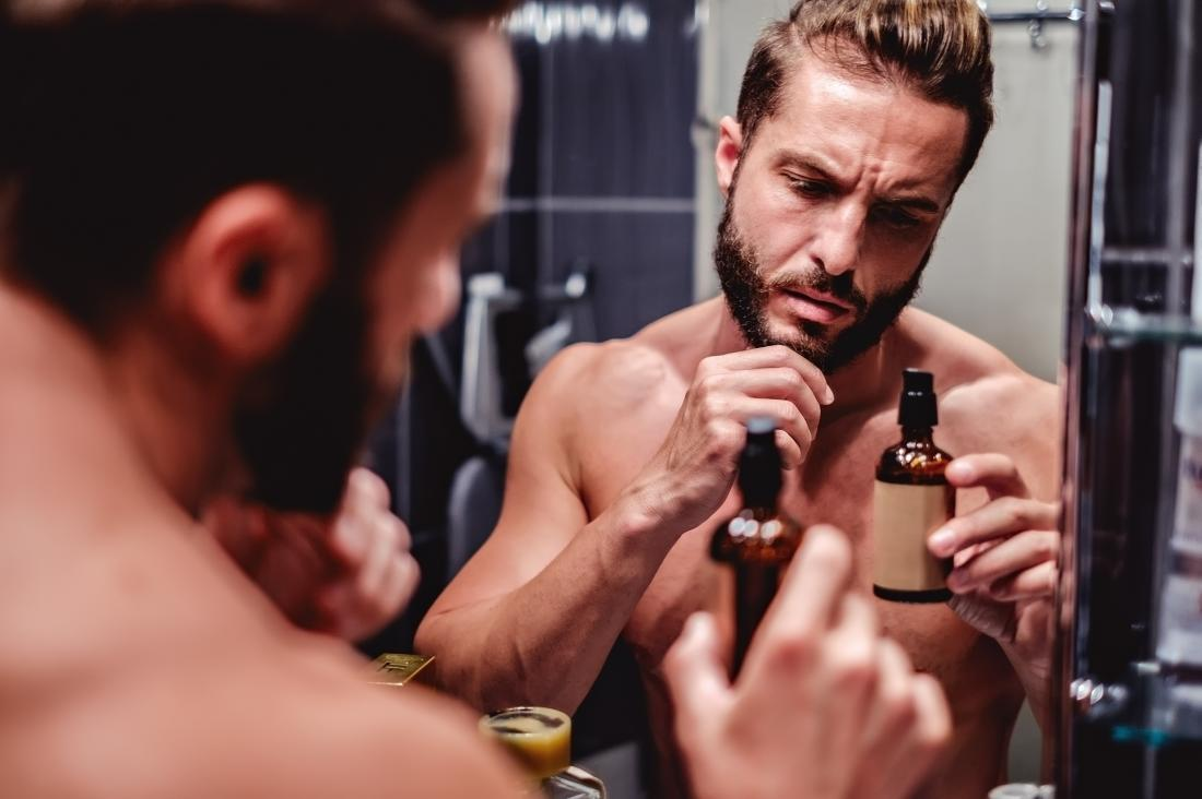 A man with dry skin and an itchy beard in front of bathroom mirror looking at facial oil bottle.