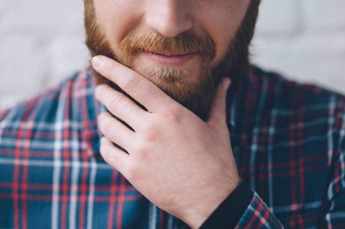 Man with itchy beard touching his chin.