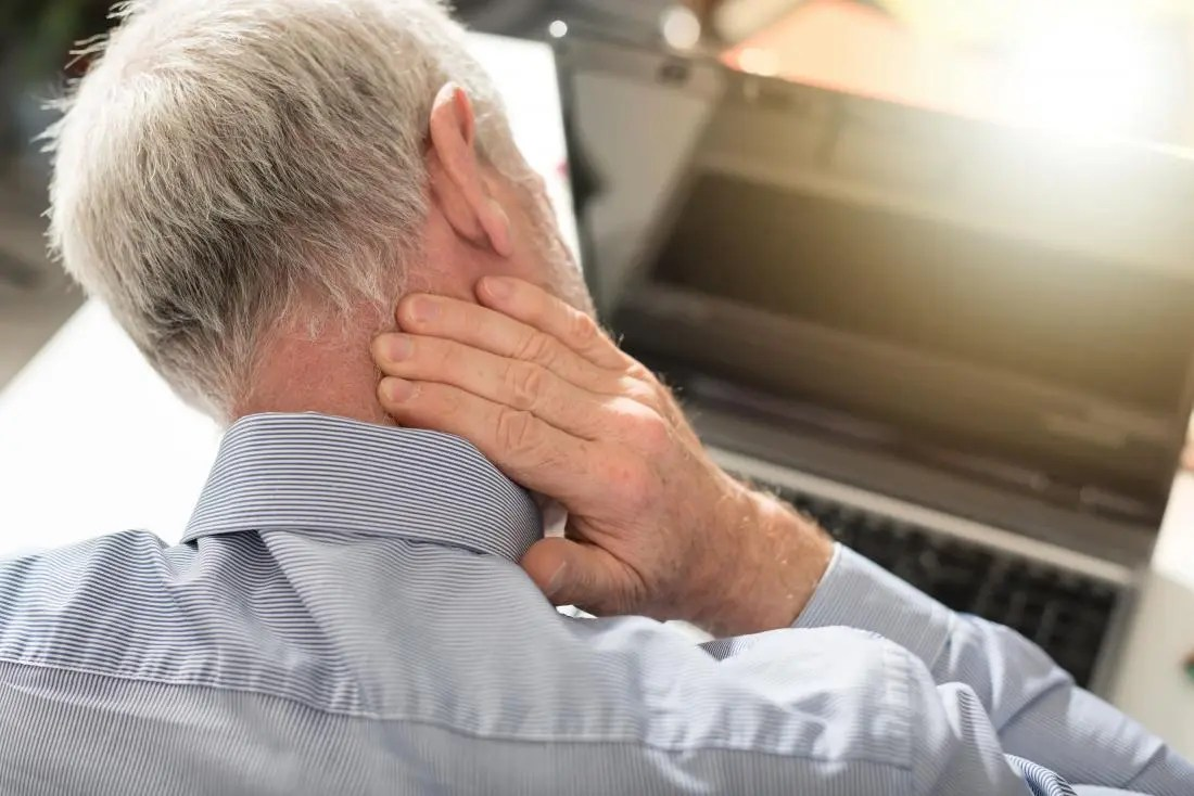Man with headache pain at back of head rubbing neck.