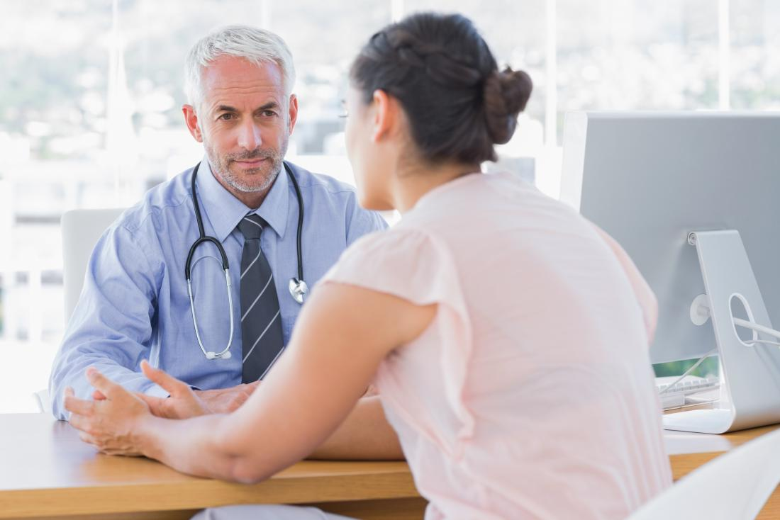 Female patient speaking to male doctor in his office.