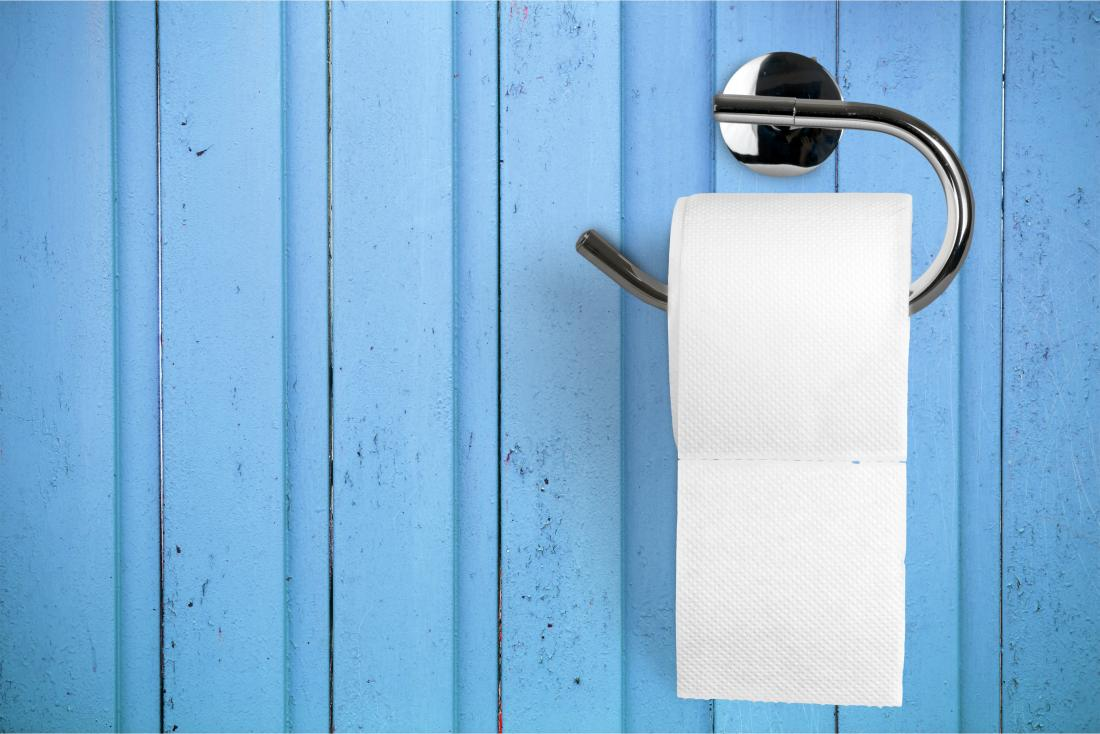 Toilet paper on holder on blue wall representing blood when wiping