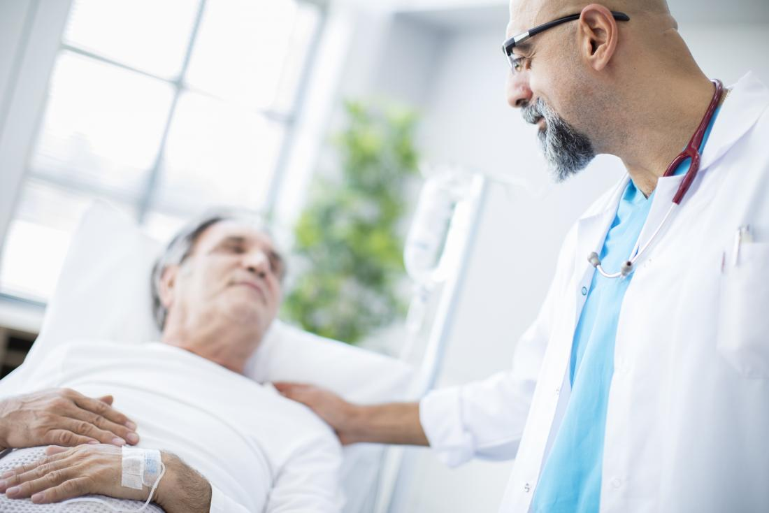 Ill senior patient in hospital bed looking up at friendly doctor.