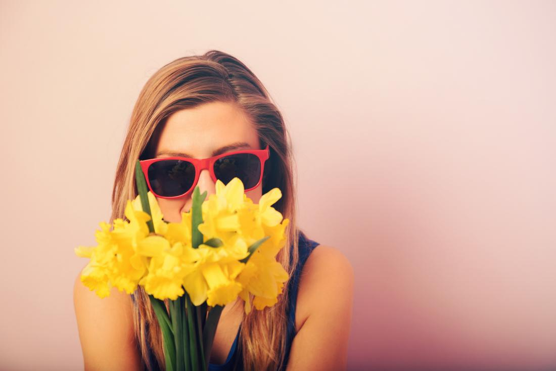 woman sniffing daffodils