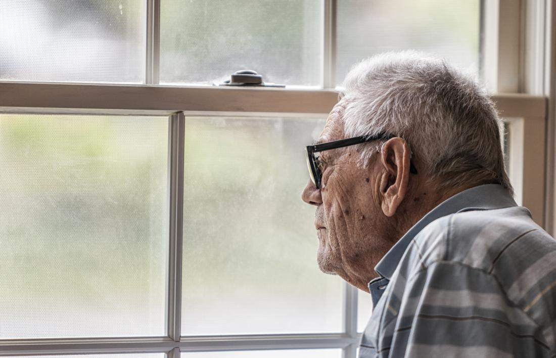 Old man with dementia looking out of window.