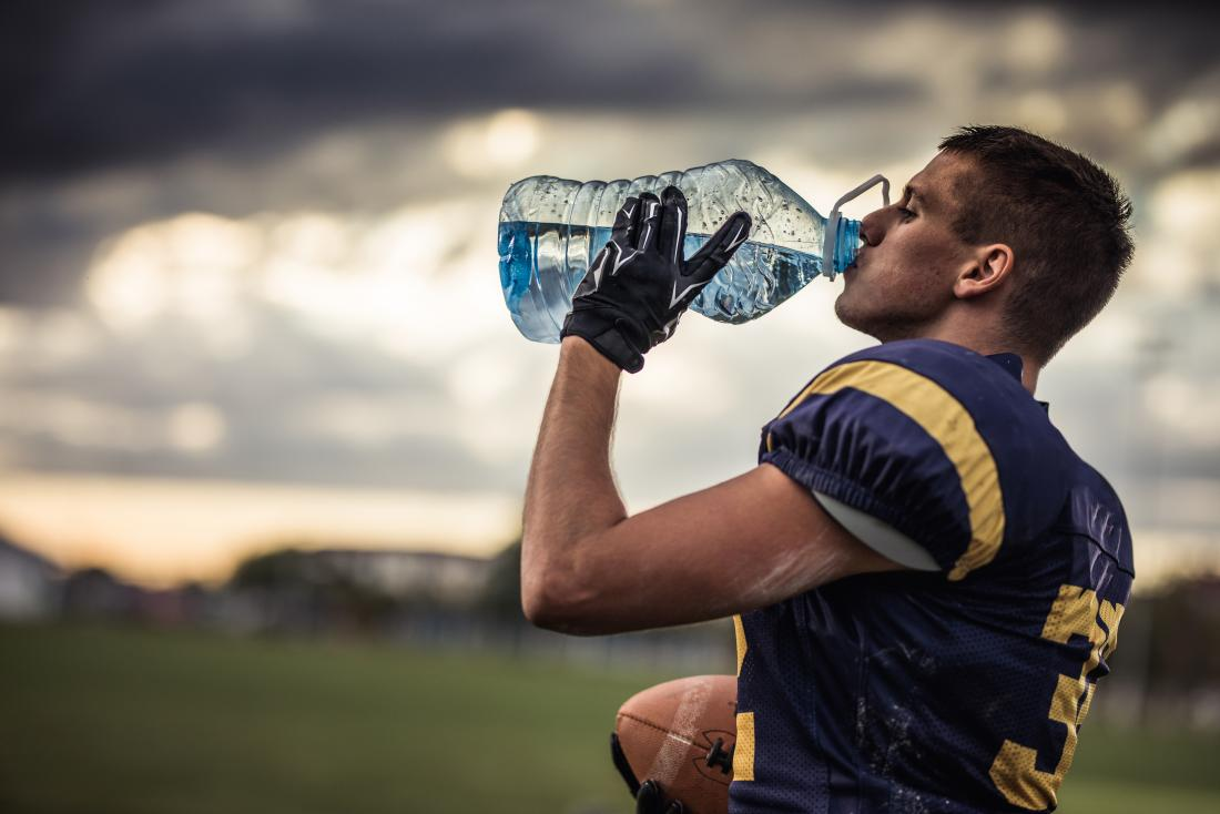 Thirsty football player drinking water from a large bottle