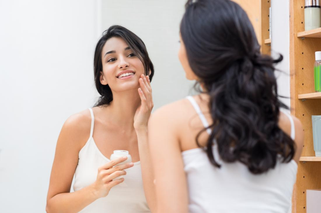 kadın yağlı cildi nemlendirici uygulayarak