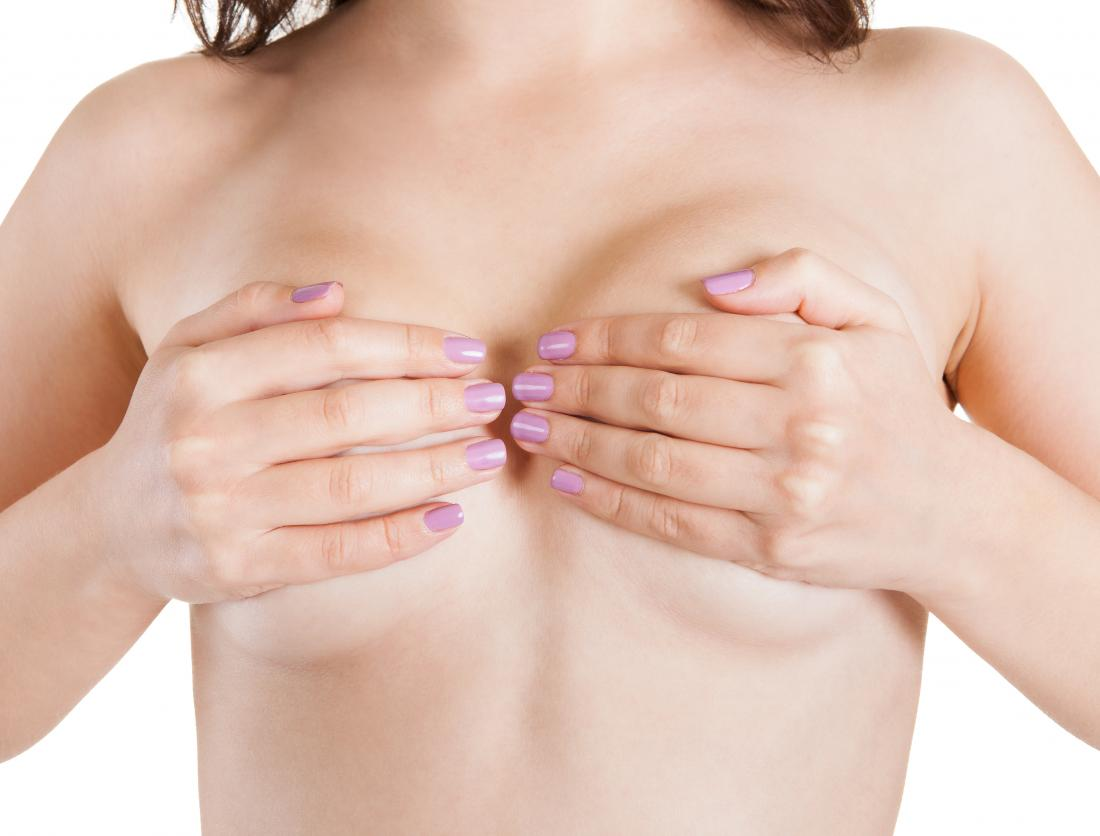 naked woman covering breasts with her hands