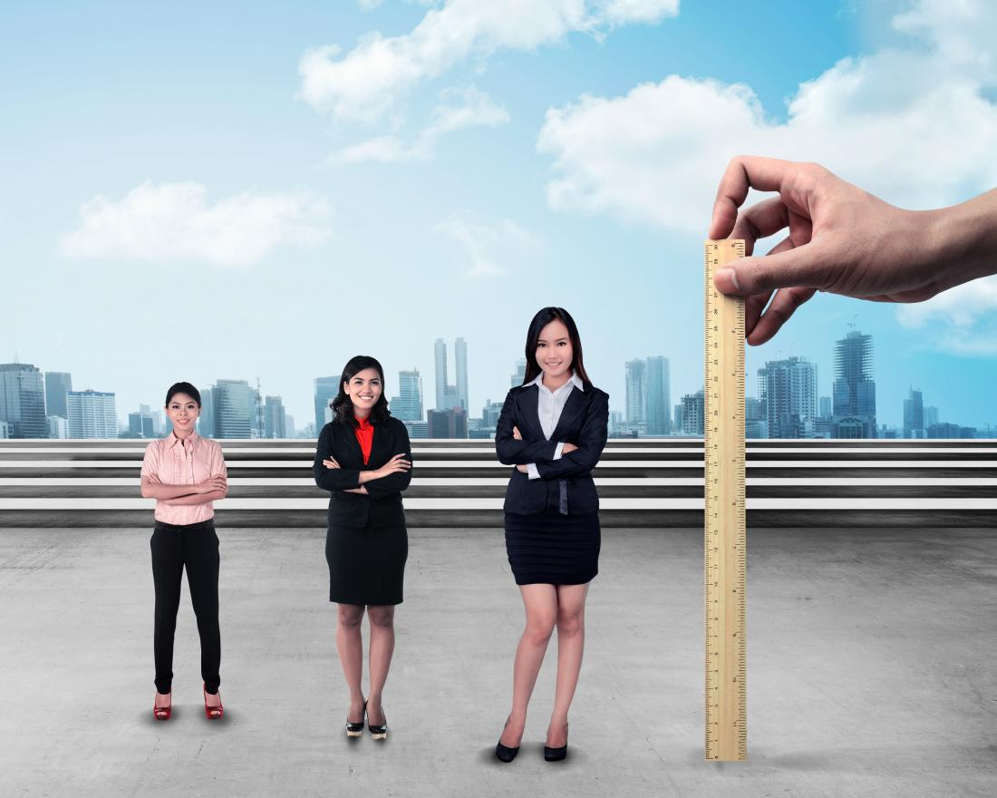 Women of different heights next to a ruler trying to work out average height for women