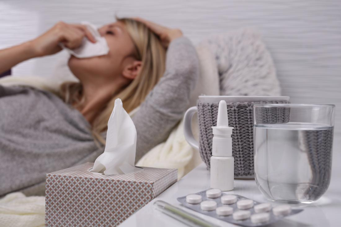 Woman suffering from cold and flu getting rid of phlegm and mucus using tissues, water, nasal spray, and medication.