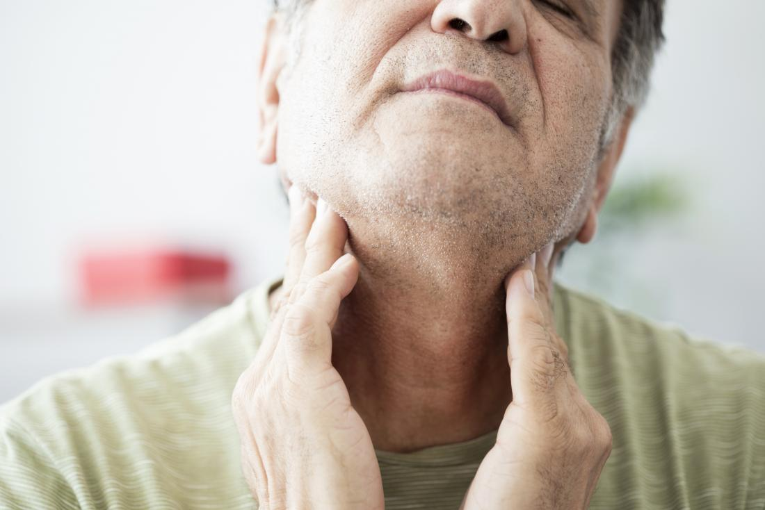 Sore throat on one side in man holding sides of neck.