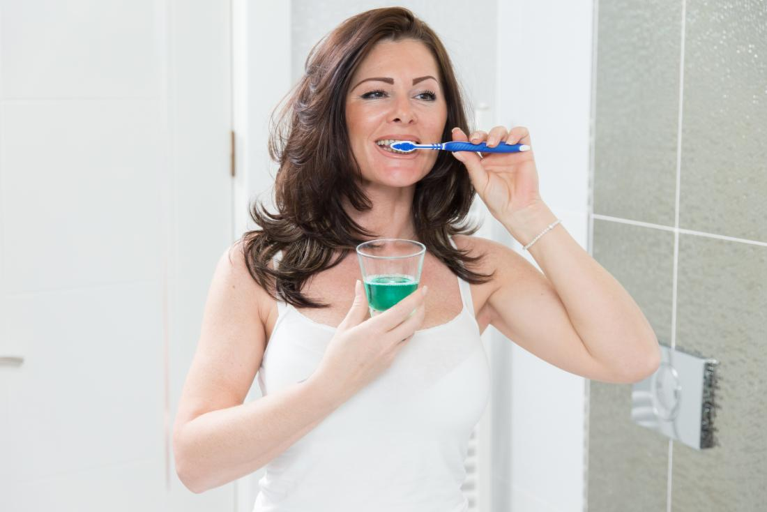 woman cleaning her teeth and holding glass of mouthwash