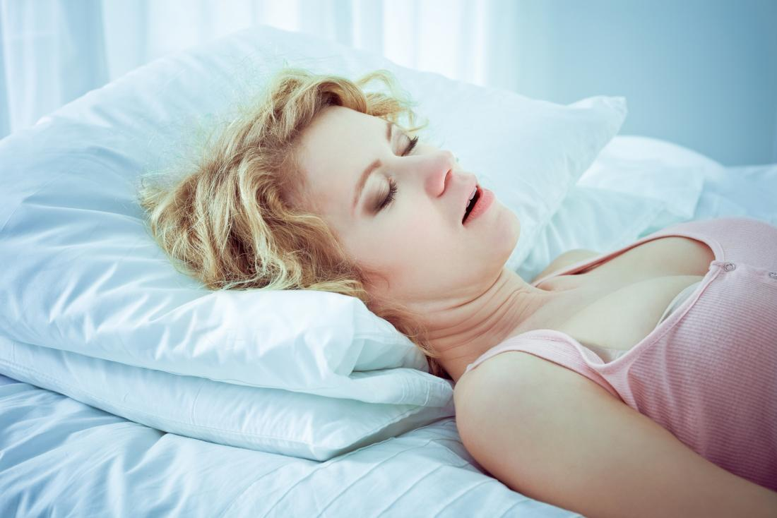 Woman trying snoring home remedies while sleeping on bed.