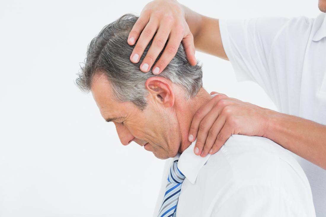 Man having neck manipulated by chiropractor during physical therapy.
