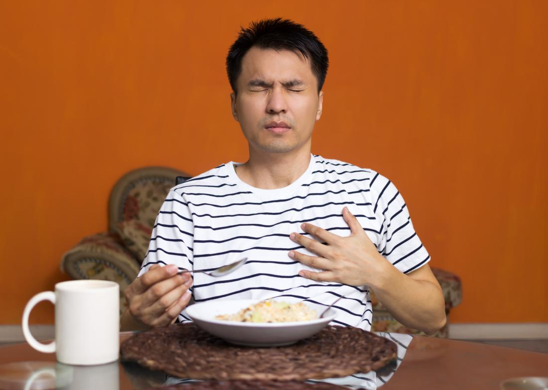 Man eating food suffering from acid reflux, touching chest in pain.