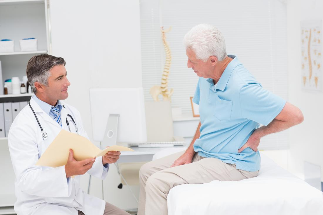 Senior man in chiropractors office explains middle back pain to doctor.