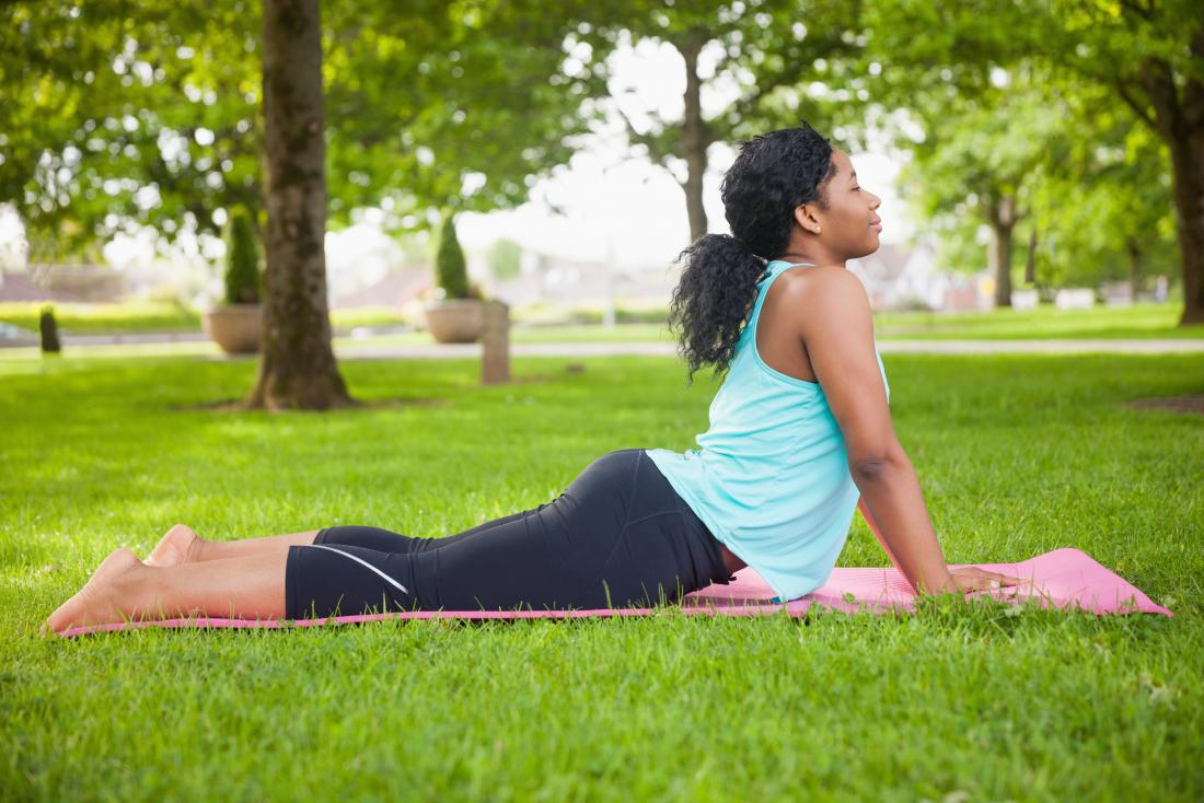 Woman outside on yoga mat in cobra pose.