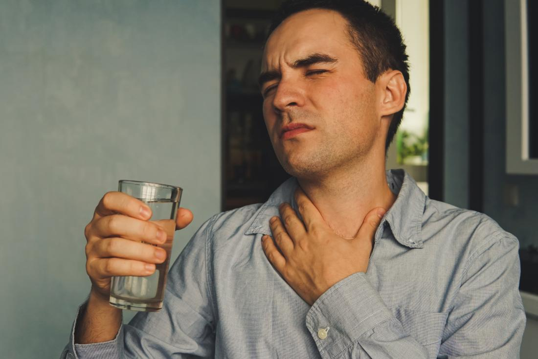 Mn with dry throat clutching his neck in pain, and holding a glass of water.