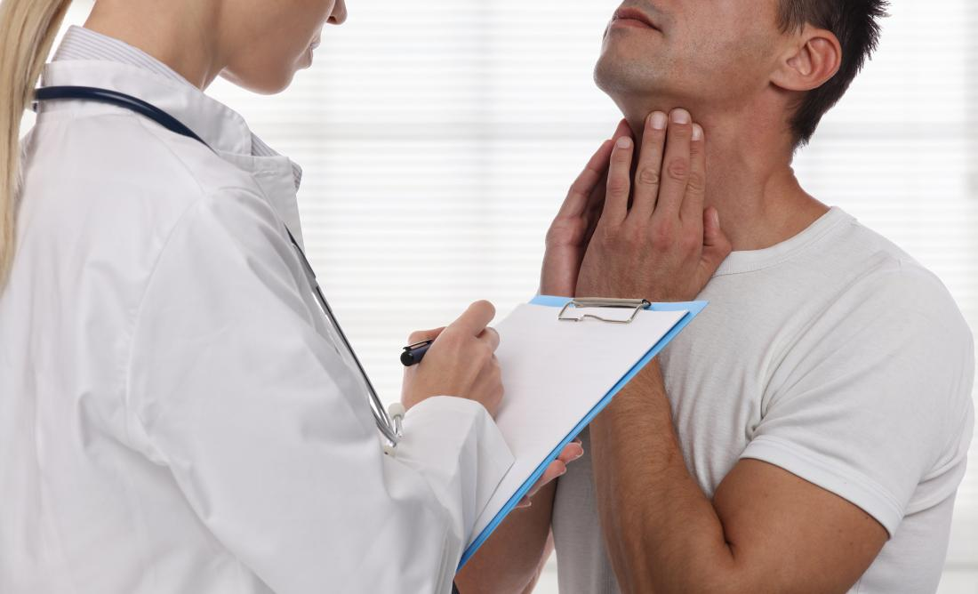 Male patient explaining problem with throat and neck to female doctor with clipboard.
