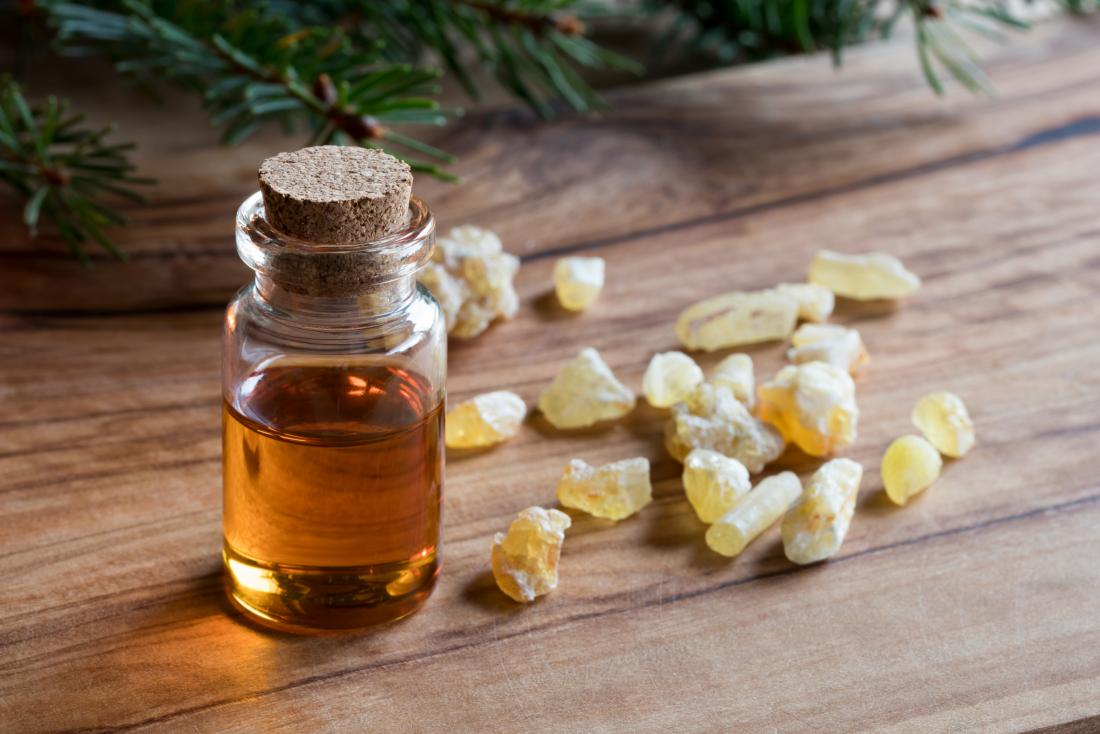 Frankincense essential oil in bottle on wooden table next to crystals.