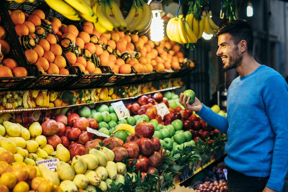 smiling man shopping for fruit