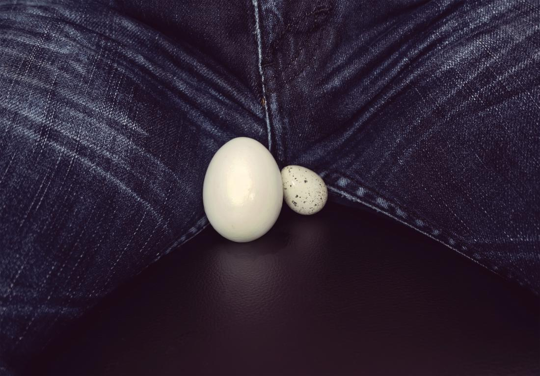 One testicle bigger than the other shown by two different sized eggs in front of close up of man's crotch in jeans