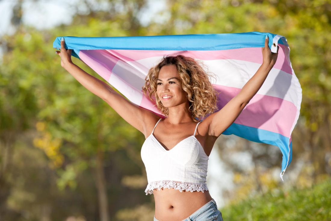 trans woman holding flag