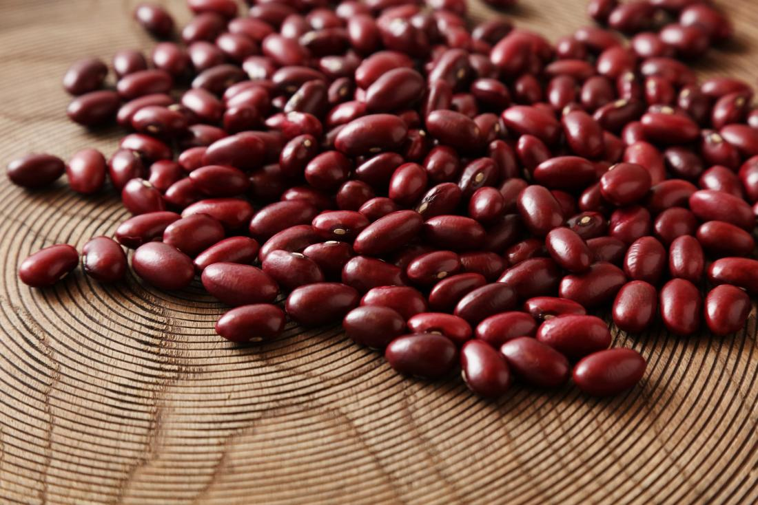 Kidney beans scattered on wooden surface.