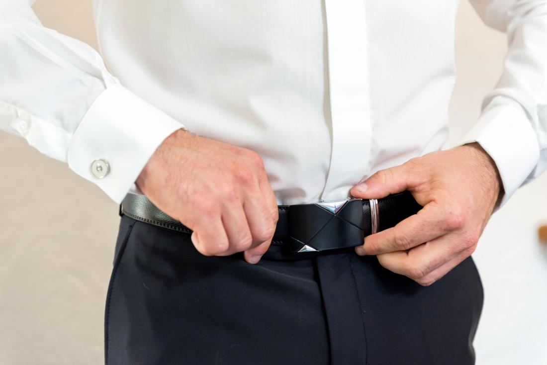 Man with white bumps on his penis tying his belt up.