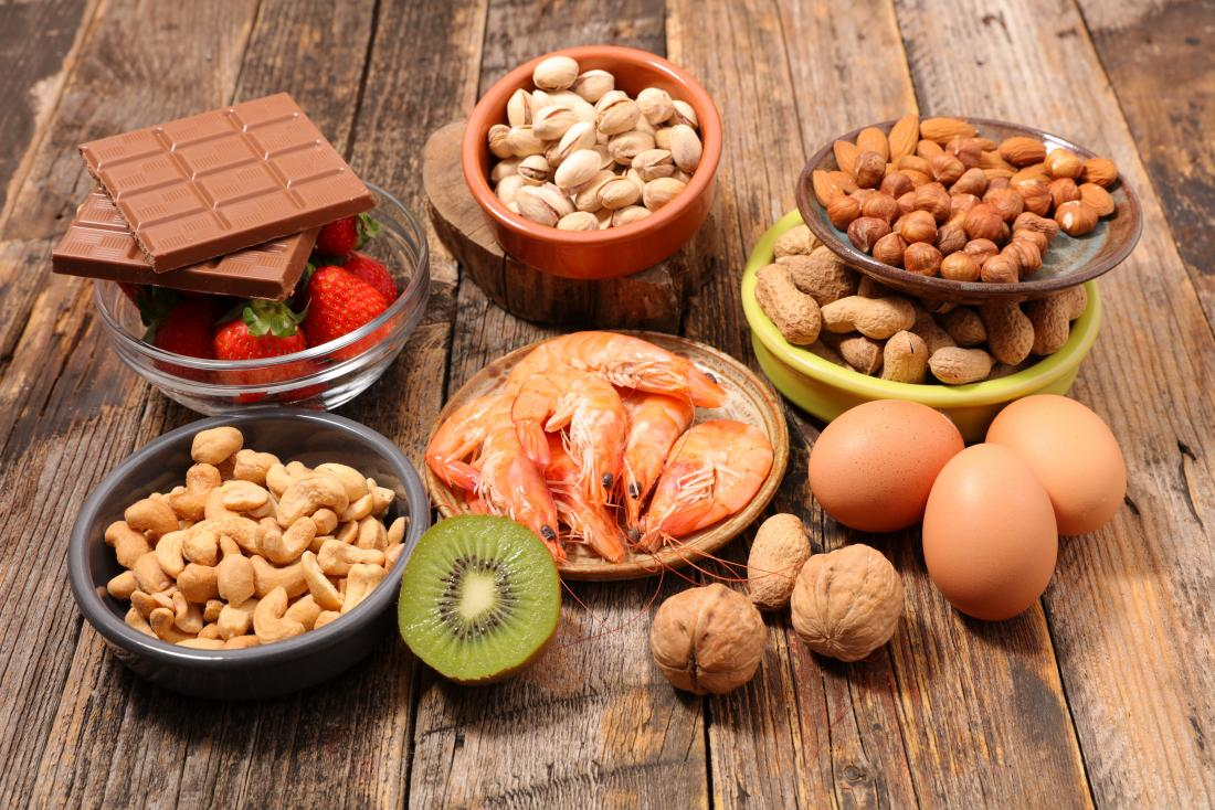Allergy foods laid out on wooden table, including cashew nuts, pecans, hazelnuts, almonds. chocolate, strawberries, shellfish, walnuts, eggs, and kiwi.