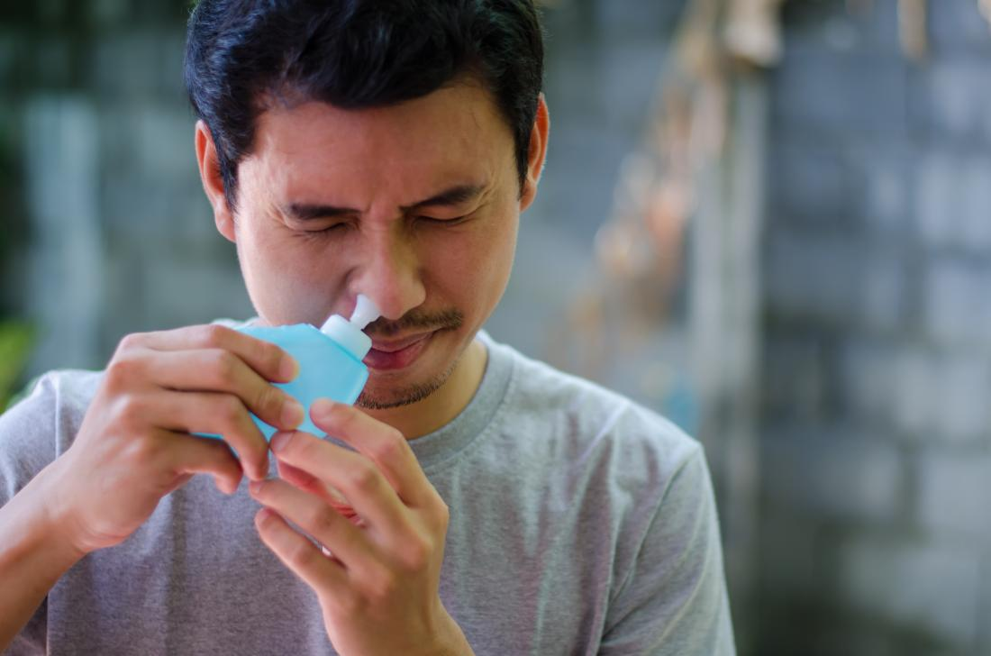 Man using neti pot to relieve sinus pressure.