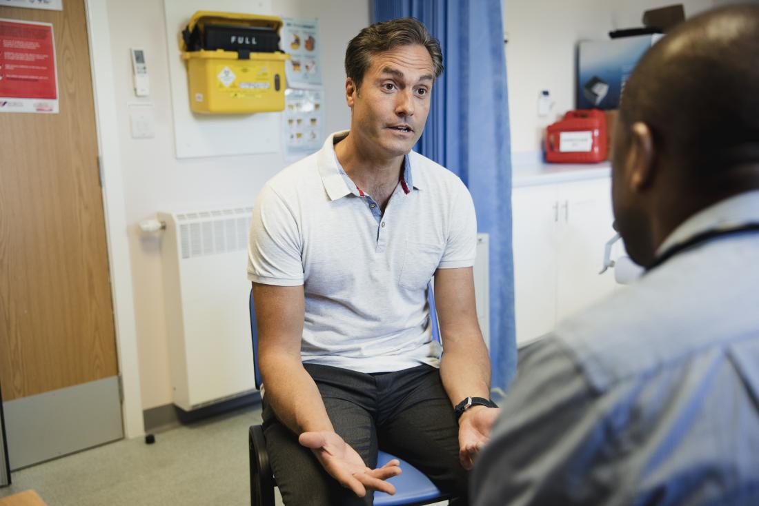 Man discussing health problem in doctor's office with doctor in foreground.