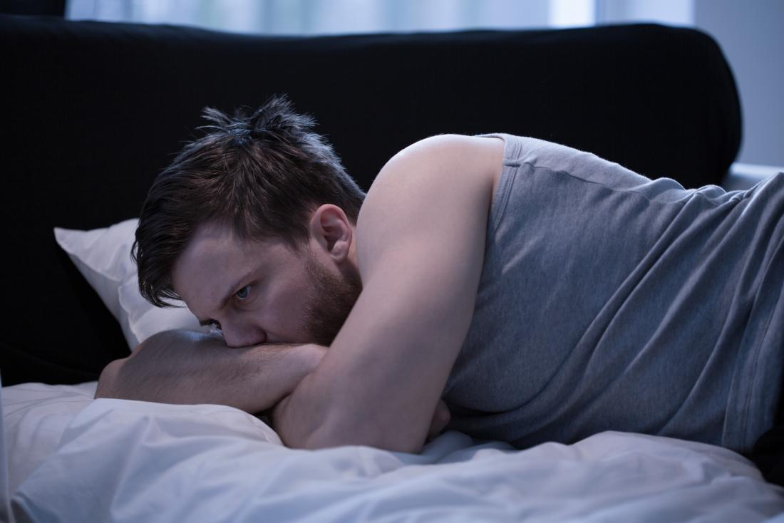 man awake in bed with possible wet dream