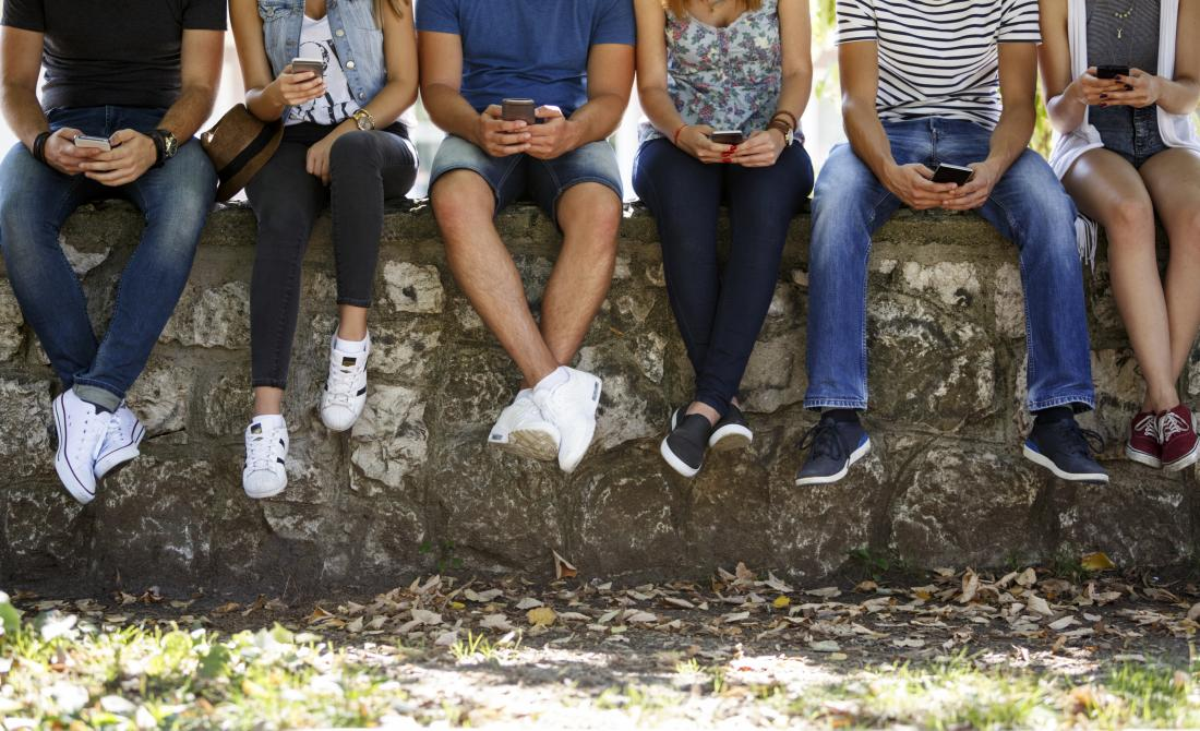 Teenagers sitting on a wall with smart phones in hand