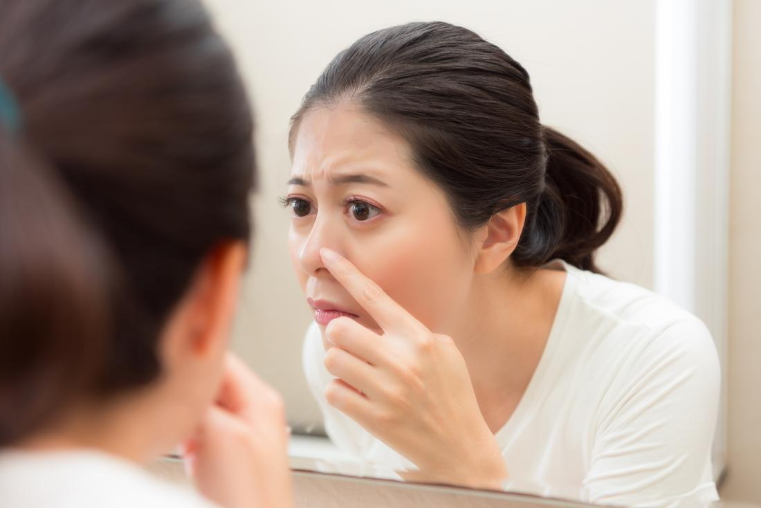 Woman inspecting whitehead on nose in bathroom mirror.