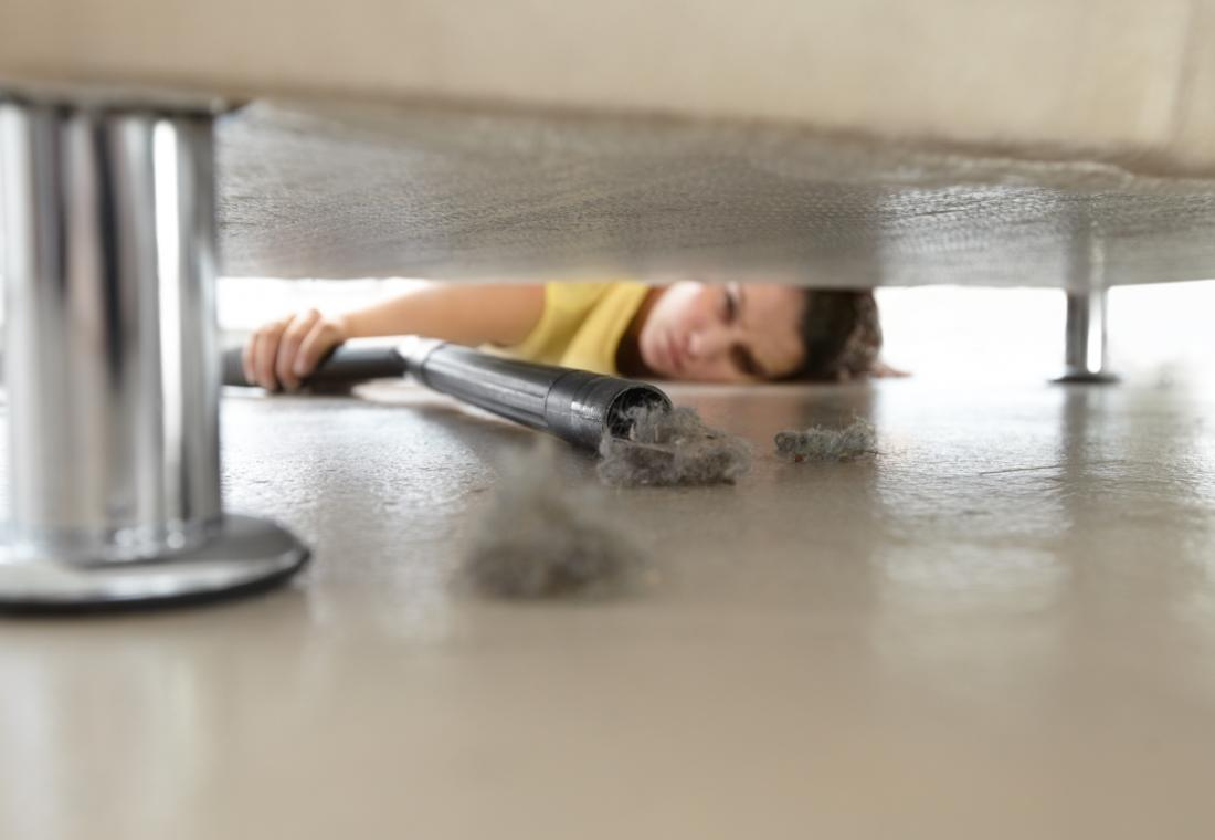 woman hoovering under her sofa which may stop allergic reactions on the face