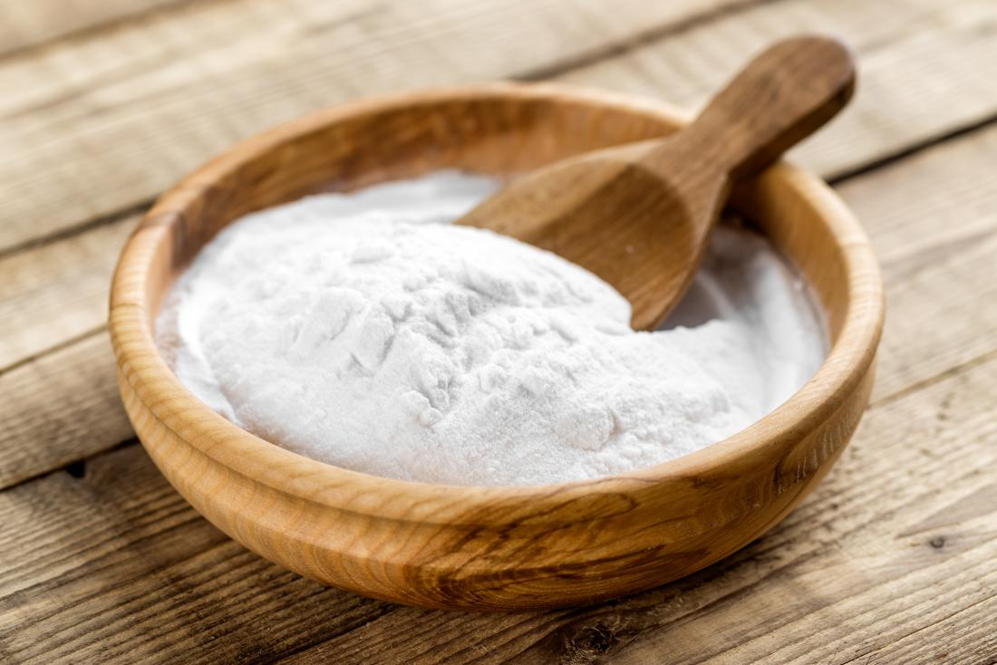 Baking soda for bath in wooden bowl with wooden spoon