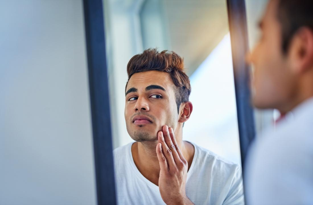 Man wanting to prevent pimples looking in mirror