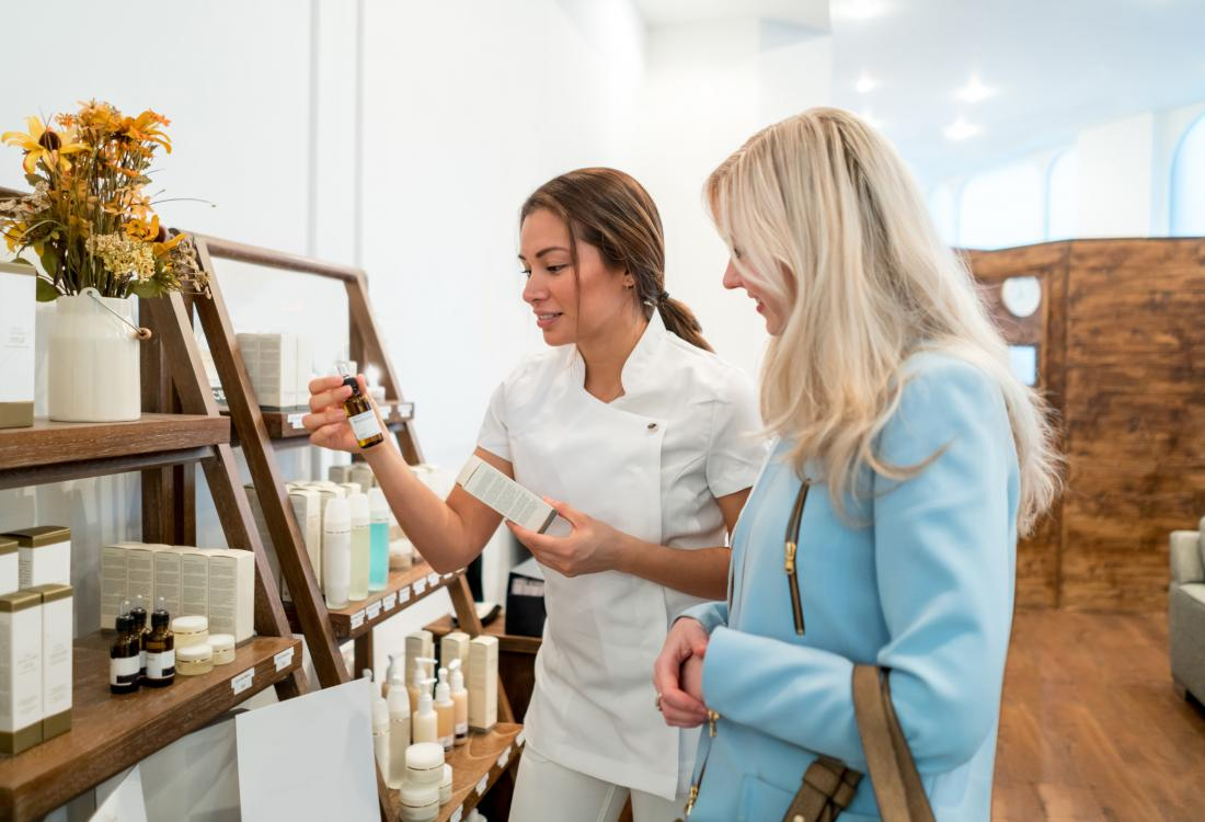 Woman shopping for skincare products receieving help from spa worker.