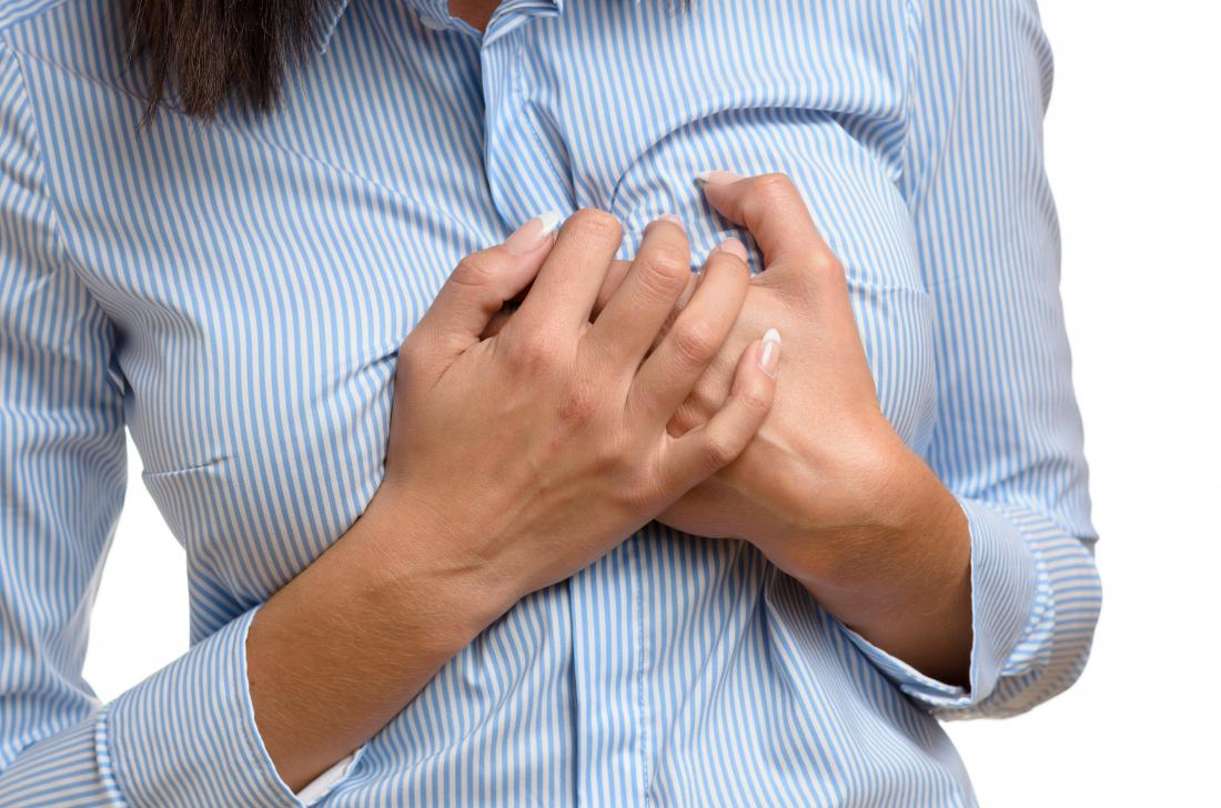 woman holding chest due to bubbling feeling in chest