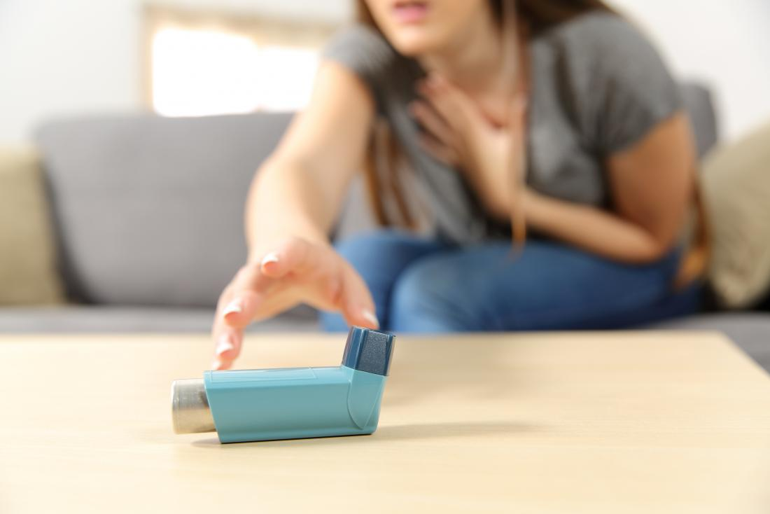Woman with asthma reaching for pump looking for emergency home remedy for asthma attack