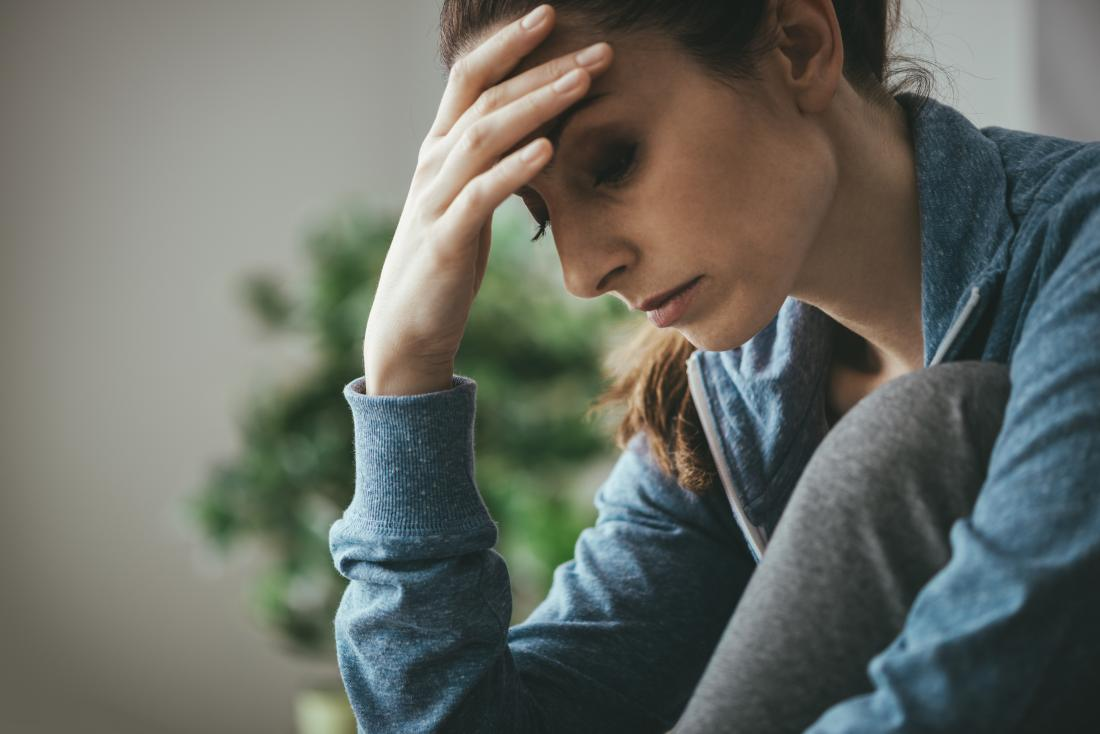 Woman with endometrial fatigue holding head and looking tired and sad.