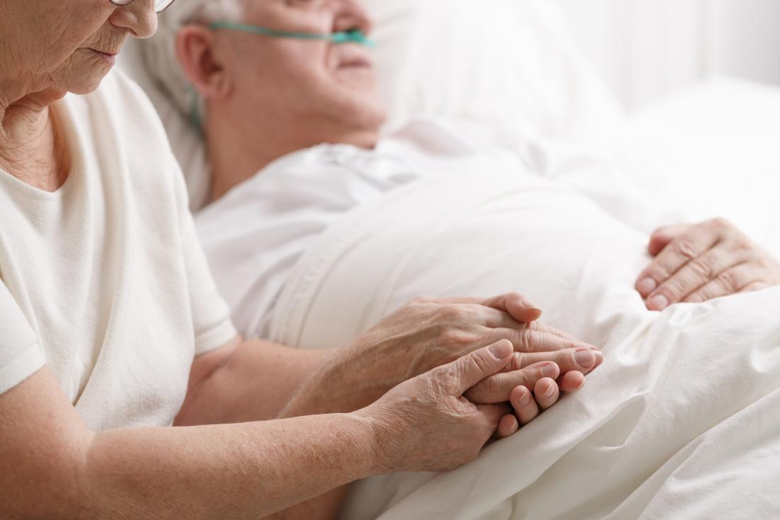 Woman holding hand of dying partner in hospice bed to demonstrate death rattle.