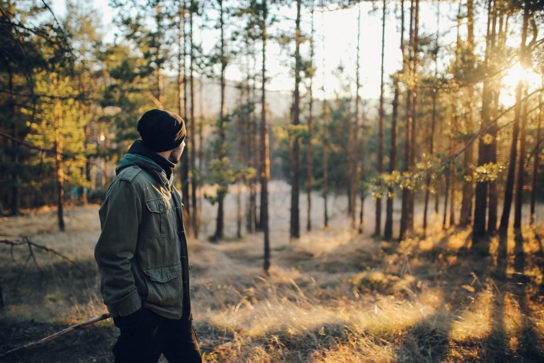 Man walking alone in forest outdoors to treat panic attack.