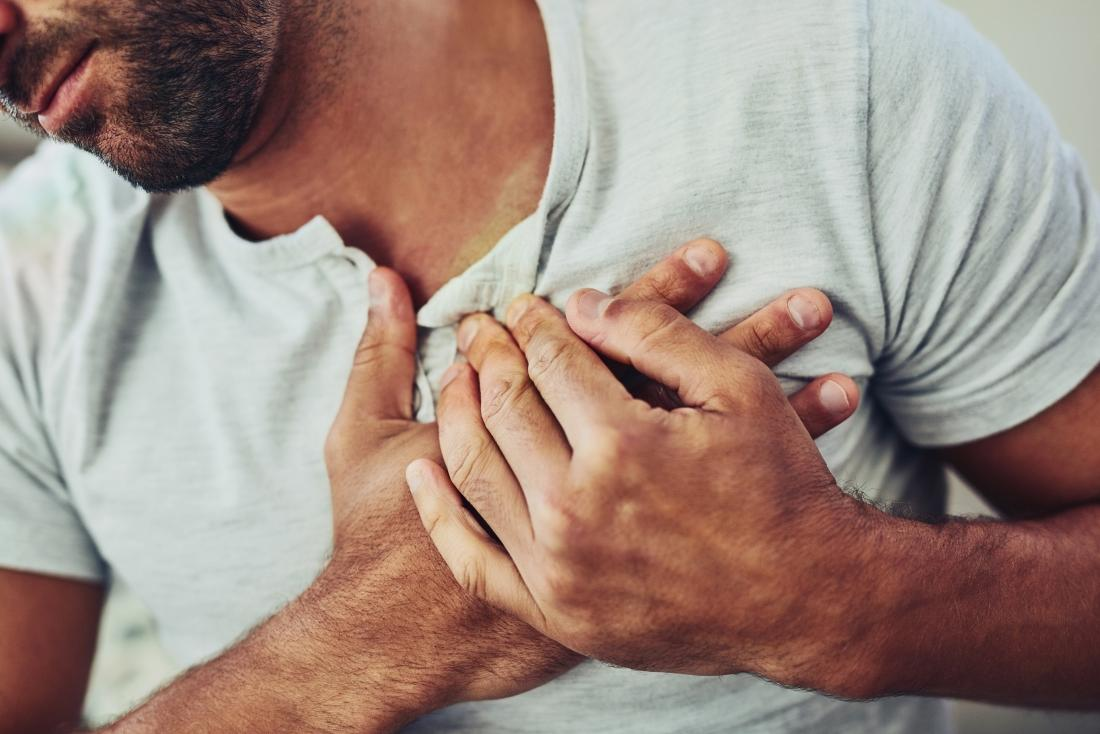 Man with chest pain clutching heart